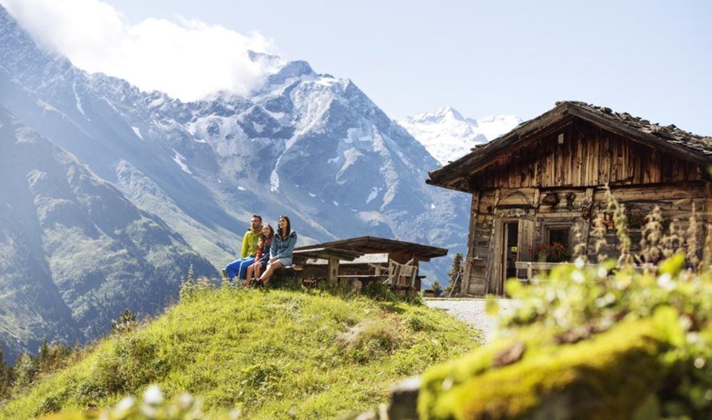 Tres persones descansant en una casa de fusta a la muntanya d'Àustria