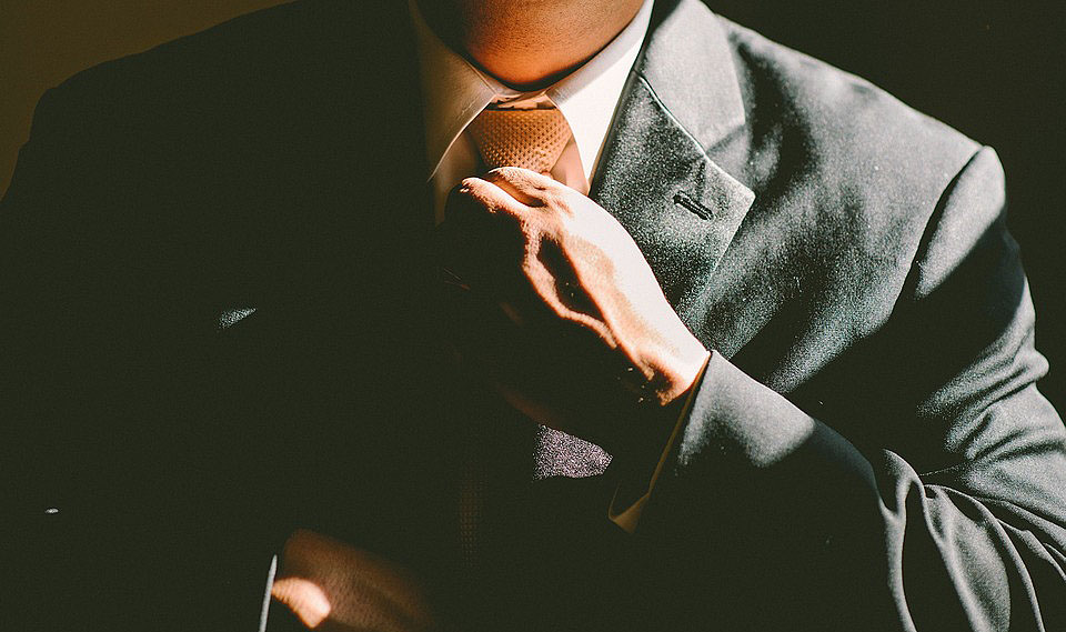 Un home ajustant-se el nus de la corbata